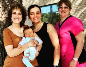 Midwife Cathy Rude, CPM, LM and student midwife with their client and sweet baby at their postpartum visit.